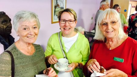 Volunteers tuck into tea and cake at the celebration. Picture: John Francis