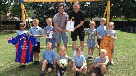 PE subject leader Tom Robinson, footballer Darren Ward, and pupils from Woolenwick Infant and Nurser