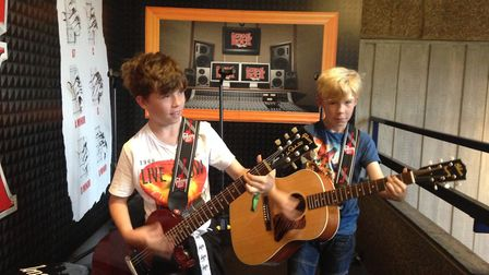 Rowan and Finn trying out guitars at the School of Rock show.