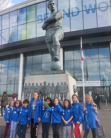 Hitchin Belles FC next to the Bobby Moore statue at Wembley