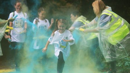 Volunteers from Guide Dogs UK cover participants in coloured corn flour at the colour station of the