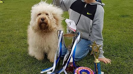 Ten-year-old Rory Hennah with Cockapoo Rolo posing with their rosette, trophy and cup. Picture: Jenn