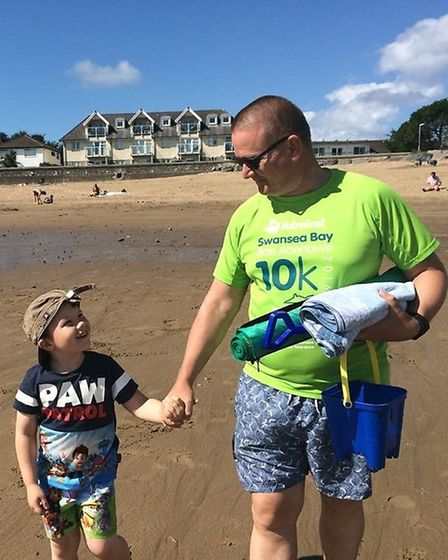 Paul Scanlon and grandson Anton take a walk along the beach after the Swansea 10k. Picture: Courtesy