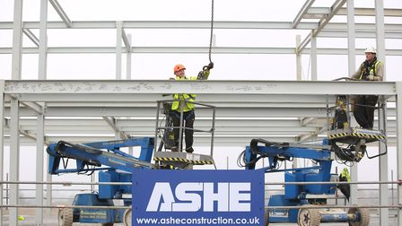 The final steel beam of the Park Place development is lifted into place and secured using special go
