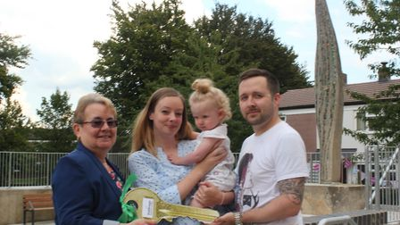 Jeanette Thomas with a family outside their new homes at Archaer Road.