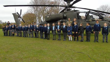 Pupils line up next to the Apache helicopter in the school field.