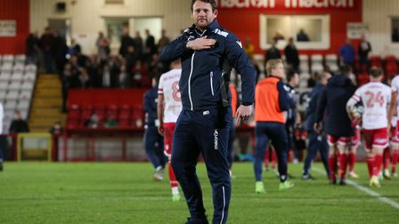 Stevenage manager Darren Sarll points to the badge as he claps the fans. Picture: Danny Loo