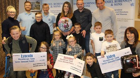 Daniel Robinson and Sons funeral directors hand over three cheques to three families with children a
