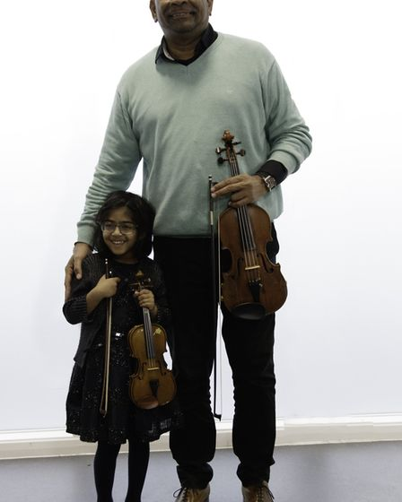 Cuban violinist Omar Puente with five-year-old Dija at Hitchin Violin School. Picture: Gary Durham