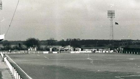 Stevenage's North Terrace with its pylon floodlights in 1968, with a flag flying from one of the pyl