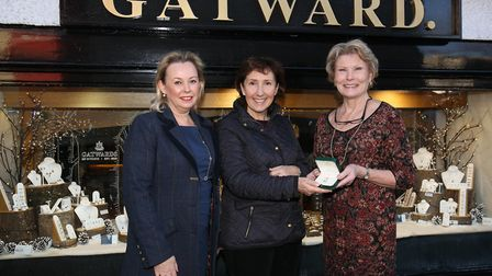 Winner Vanessa Cole (centre) is presented with the blue topaz pendant by Tilehouse Counselling patro