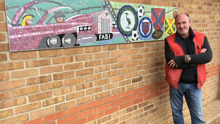 Artist Oliver Budd with the TV, film, sports and recreation mosaic. Picture: Central Beds Council