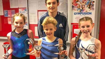 Coach Charlie Jefferies with gymnasts Emily Halford, Carter Fenn and Zoe Cooper. Picture: Courtesy o