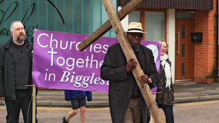 Cross-bearer Olu Osibowale and Churches Together banner during the Good Friday Walk of Witness by Ch