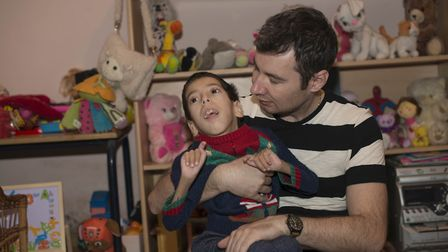 Humanitas physiotherapist Radu gives treatment to Loan in his foster home. Picture: Humanitas