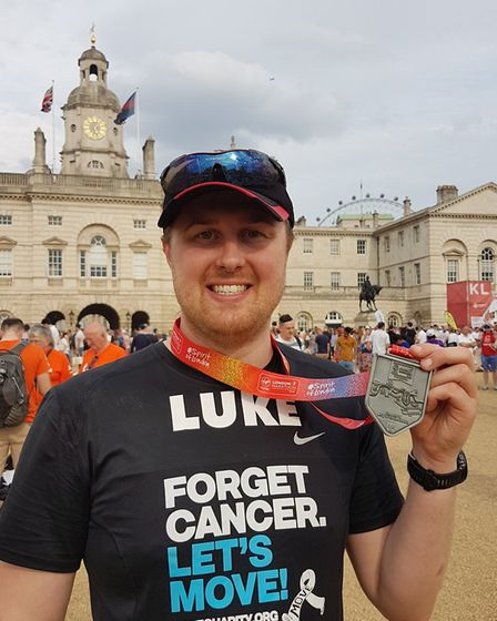 Luke Green celebrates with his medal after running the London Marathon. Picture: Sarah Green