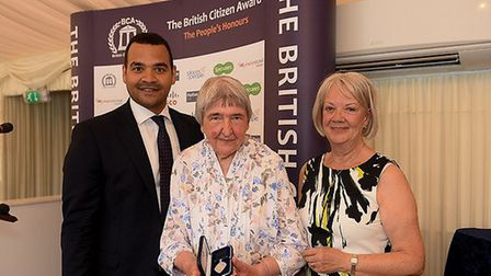 Yvonne Limbrick, centre, receives her British Citizen Award from Dame Mary Perkins and Michael Under