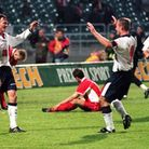 Alan Shearer congratulates an elated Teddy Sheringham on scoring the second goal, which secured the