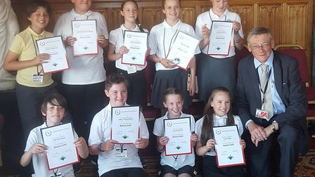Children from Hitchin's Highover School show off their bronze-level bridge certificates, alongside L