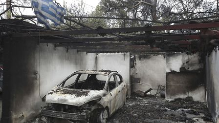 A Greek flag flutters over the charred remains of a burned-out car and house in Mati, east of Athens