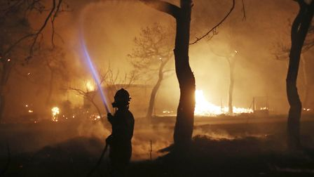 A firefighter sprays water on the fire in the town of Mati, east of Athens. Picture: AP/Thanassis St