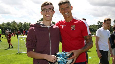 Alex Revell gives a pair of his boots to Stevenage fan Aaron Hattam at the Stevenage FC Open Day 201