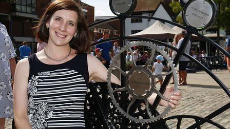 Charlotte Gatward with the plaque on the Gatward bench in Hitchin Market Place celebrating her joini