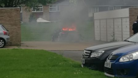 The burning Audi A5 involved in the collison with a police officer in Sandy. Picture: Steven Dando