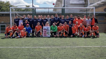Mike Quinlan's daughter Olivia poses with the teams and a picture of her dad ahead of the charity fo