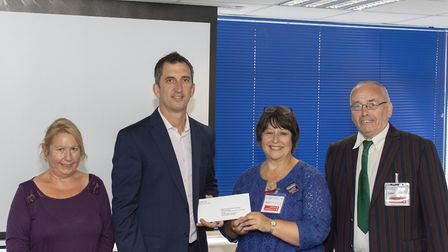 Crane's Scott Dalrymple hands over a donation to Letchworth-based charity Growing People. Picture: J