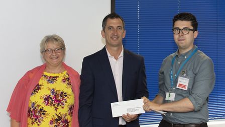 Crane's Scott Dalrymple hands over a donation to the Sue Ryder St John's Hospice based in Moggerhang