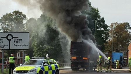 Firefighters tackle the freight lorry fire in Hitchin's Fishponds Road, as police overlook the scene