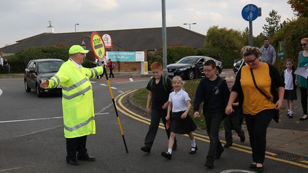 Round Diamond School crossing patrol person Terry Tyler helps families cross the road outside the sc