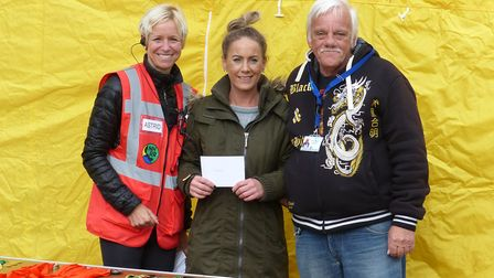 North Herts Road Runners chairperson Astrid McKeown presents a cheque to Zoe Theakston and Barry fro