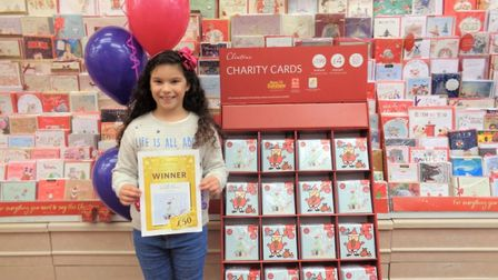 Isabelle Fornari, eight, with her £50 voucher prize and her Christmas card design on sale in Clinton