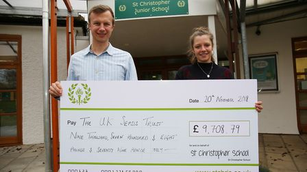 St Christopher School parent Philip Fielding presents a cheque for over £9,000 to press and communic