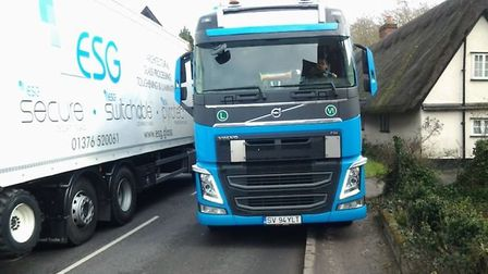 Two lorries passing side-by-side in Cottered, at the A507's narrowest point. The road is 5.1m wide,
