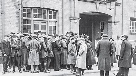 Members of the public and service personnel wait outside Hitchin police station on March 11, 1919, a