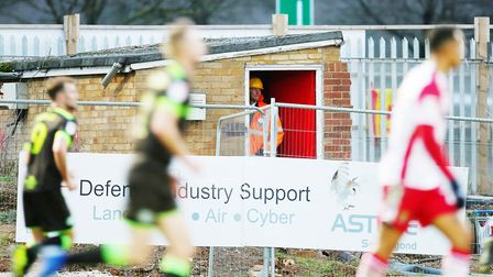 A man watches the game from a brick hut where the North stand will be built in the League Two game b