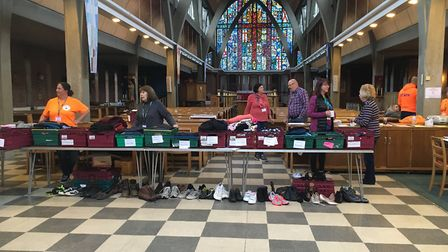Volunteers setting up clothing stands for the Feed Up Warm Up drop-in in Stevenage. Picture: Matt Po