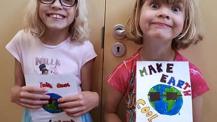9-year-old Maya Jones and Willow Jones, 6, with their climate-themed artwork. Picture: Sarah Royston