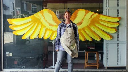 Clara Nicoll posing in front of her hand painted golden wings in Churchgate. Picture: Clara Nicoll