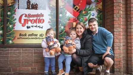 Twins, Niamh and Cc Ledere, two, hug their new teddies at Santa's Grotto, with mum Vicky and dad Pau
