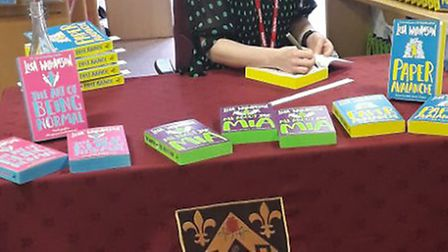 Author Lisa Williamson signing copies of her books: The Art of Being Normal, All about Mia and Paper