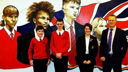 Headteacher Geraint Edwards (R) poses with students in front of the mural. Picture: Clara Nicoll