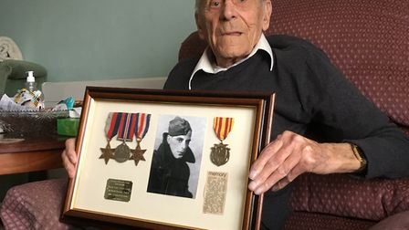 George Clark relaxing at home with his war medals