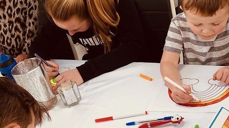 Carly and her children painting rainbows. Picture: Carly Stacey