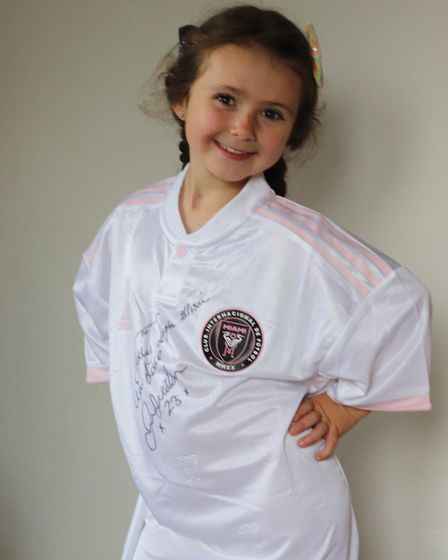 Five-year-old Betty cycles wearing a different football shirt every day. Picture: Faye Allinson
