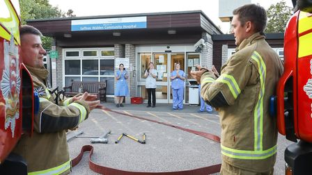 Fire chief Paul Curtis (left) leads his crew in the final clap for carers at Radwinter Road Communit