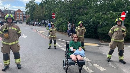 Caroline, flanked by firefighters, watched a Spitfire fly over the hospital on the 72nd anniversary